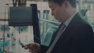 Geschäftsmann mit Handy im Bahnhof