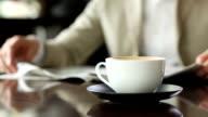 Geschäftsmann mit Kaffee und Tageszeitung