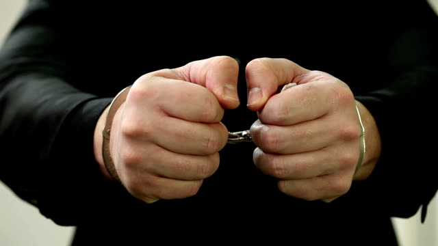 Businessman with handcuffs showing money.