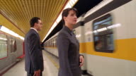 Businessman + woman standing on platform in subway station as train arrives / they enter / Milan
