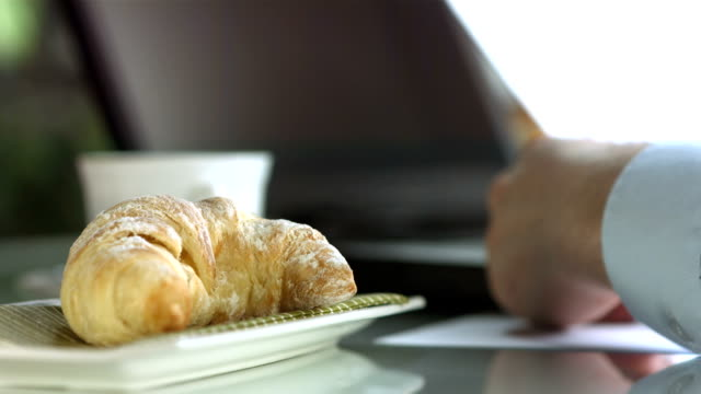 HD DOLLY: Businessman Working During Breakfast