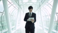 MS Businessman working on a digital tablet in modern office building.