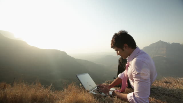 Businessman working on a laptop on the cliff of mountain