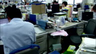A businessman works at his desk among stacks of binders, Japan. Available in HD.