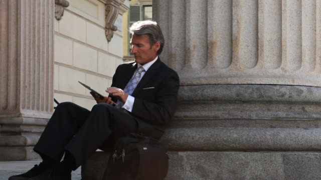 Businessman works on digital tablet at base of column