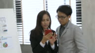 Businessmen and Businesswoman discussing data mobile phone in office