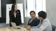 Businessmen and Businesswoman discussing tablet and laptop in office