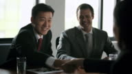 MS SELECTIVE FOCUS Businessmen and woman talking at meeting and shaking hands / China