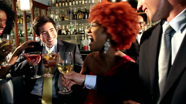 Businessmen and women with drinks at bar