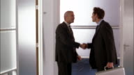 Businessmen greet each other in the hallway before entering an office.