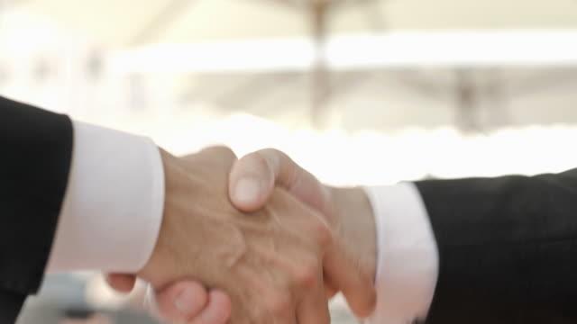 HD: Businessmen Handshaking Outdoors