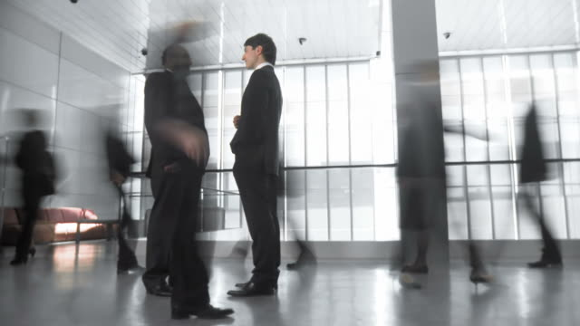 HD TIME-LAPSE: Businessmen Having Discussion In Busy Corridor