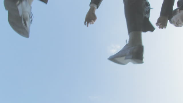 Businessmen jumping with blue sky in background