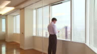 Businessmen looking out office window at city