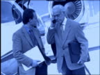 B/W 2 businessmen shake hands by jet / 1 with cellular phone / slow motion / stewardess in background