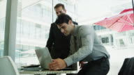 MS of businessmen shaking hands then using laptop in office