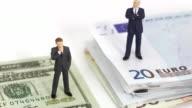 Businessmen standing on dollar bills.