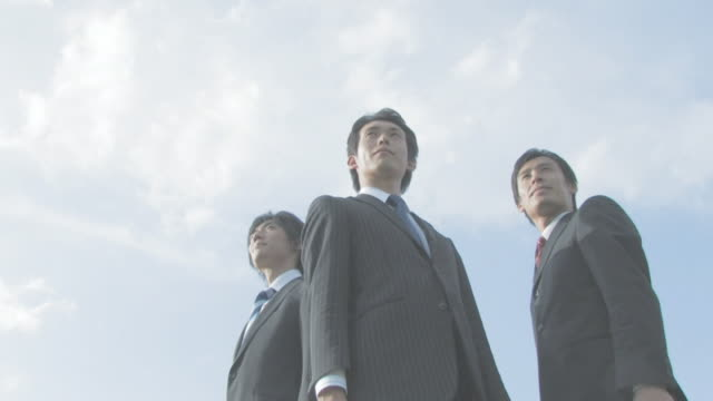 Businessmen standing with blue sky in background