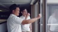 Businessmen talking at office window