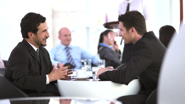 HD DOLLY: Businessmen Talking During Coffee Break
