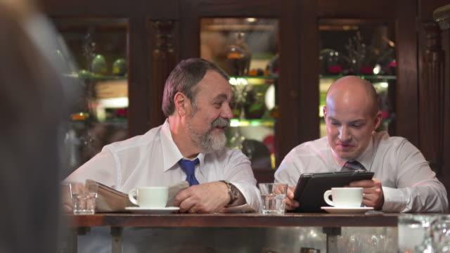 HD: Uomini d'affari con Tavoletta digitale In Bar