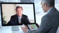 CU Businessmen Video Conferencing in Corporate Office, Discussing Financial Information / Virginia Beach, Virginia, United States