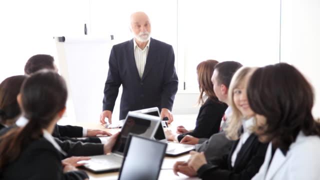 Businesspeople applauding for senior man.