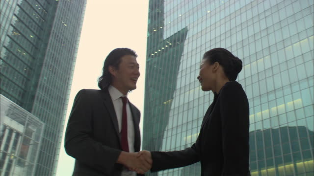 MS, LA, TU, Businesspeople shaking hands in front of office buildings, Singapore
