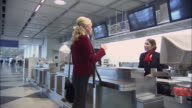 MS Businesspeople waiting in line at airport check-in counter/ PAN Check-in attendant helping customers one by one/ Munich, Germany