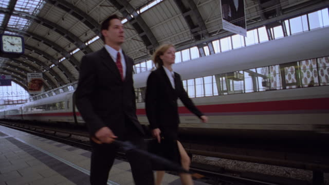 PAN businesspeople walking on platform next to moving high speed train / Berlin, Germany