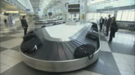 WS Businesspeople watching baggage claim carousel, then taking luggage and walking away / Munich, Germany