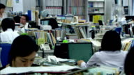Businesspeople work at cluttered desks in an open-plan office, Japan. Available in HD.
