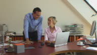 MS, Businesswoman and businessman looking at laptop in office, Berlin, Germany