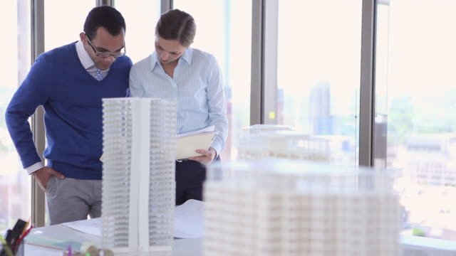 MS DS businesswoman and businessman standing in office near window examining documents architectural models in foreground