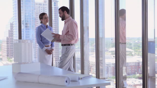 MS R/F businesswoman and businessman standing in office near window examining documents architectural models in foreground