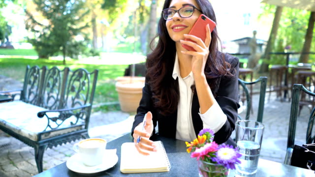 Geschäftsfrau, die Beantwortung von ihrem Telefon und Notizen im Tagebuch