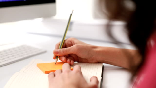Businesswoman checking notes and post it