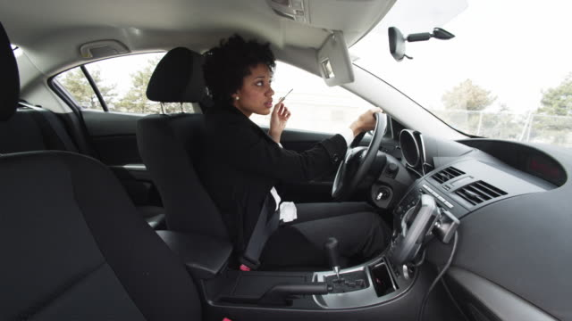 MS Businesswoman driving car and applying make-up / Orem, Utah, USA