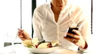 Businesswoman eating in restaurant.