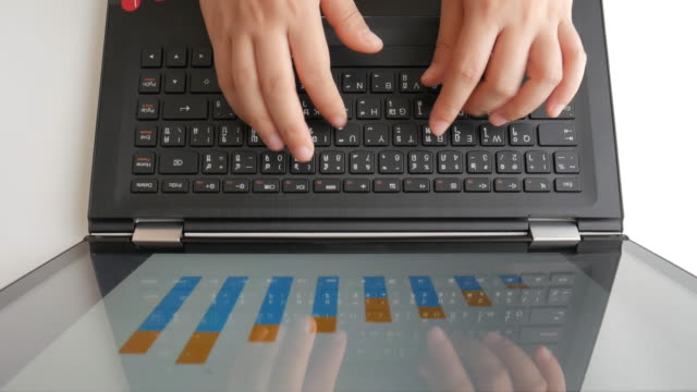 Businesswoman Hands typing on laptop keyboard for checking digital graph