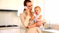 Businesswoman holding baby while talking on the phone