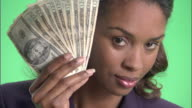ECU, Businesswoman holding fan of American dollar banknotes in front of face in studio, portrait
