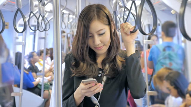 Businesswoman holding onto a handle and using smartphone on a train