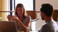 MS Businesswoman in discussion with colleagues at office conference room table