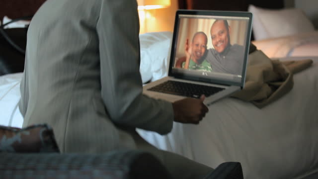 MS TU TD Businesswoman in hotel room talking to husband and son (8-9) with webcam on laptop / Richmond, Virginia, USA