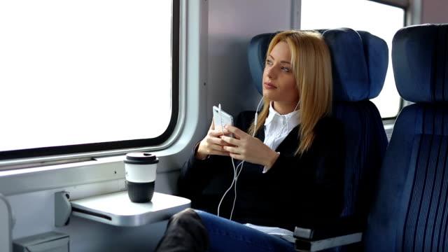 Geschäftsfrau im Zug Musik hören