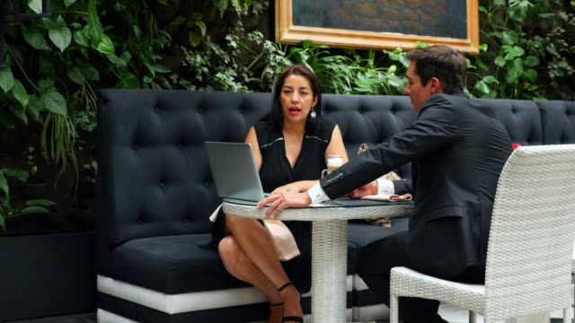 MS Businesswoman leading discussion with businessman during lunch meeting in restaurant