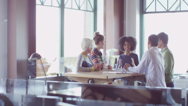 MS Businesswoman leading team meeting with coworkers at table in office