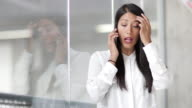 Businesswoman looking at reflection and using smartphone in an office