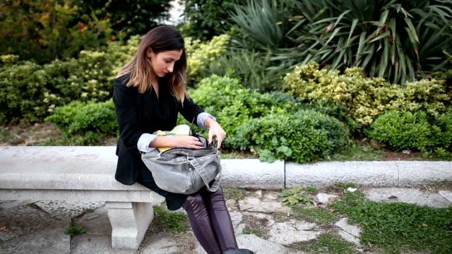 Zakenvrouw zoekt de telefoon in een zak